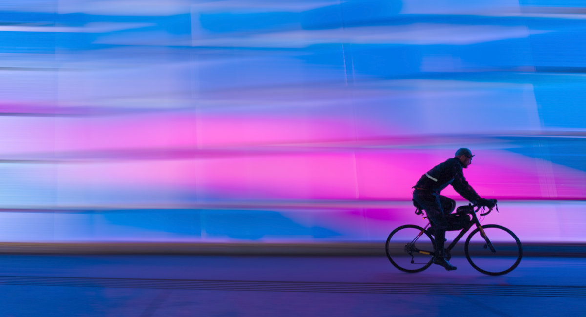 Diversity Examples, Person Riding Bike With Blue And Pink Colorful Background